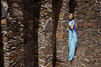 young woman in sari, peeking from behind brick pillar - Alex Mares-Manton