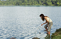 Young woman playing with stick in lake - Yukmin