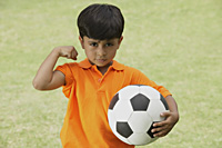 little boy showing muscle, holding soccer ball - Vivek Sharma