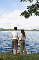Couple holding hands looking at lake - Yukmin