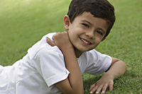 young boy resting on grass, smiling - Vivek Sharma