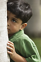 Little boy peaking up side of tree trunk - Vivek Sharma