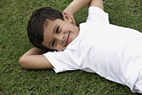 Little boy lying on back in park - Vivek Sharma