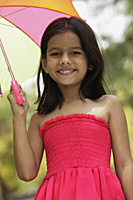 Little girl in pink dress standing under umbrella - Vivek Sharma