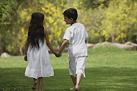 two children holding hands walking - Vivek Sharma