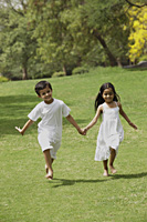 two little children running through a park holding hands - Vivek Sharma