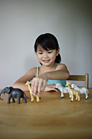 Little girl playing with plastic animals - Yukmin