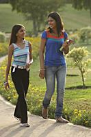 Teen girls walking through park, with books - Vivek Sharma