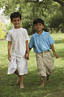two little boys holding hands in a park - Vivek Sharma
