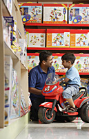 father and son in toy store - Alex Mares-Manton