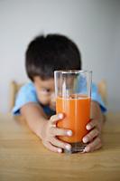 Little boy looking at glass of juice - Yukmin