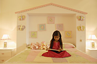 little girl reading book on bed - Alex Mares-Manton