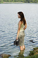 Young woman standing in shallow end of lake - Yukmin