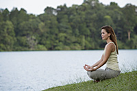 Woman meditating by lake - Yukmin