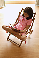 Little girl in chair reading - Alex Mares-Manton