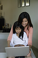 Mother and daughter working at laptop computer - Yukmin