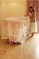 mother looking into baby crib - Alex Mares-Manton