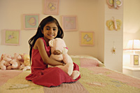 little girl with stuff bear on bed - Alex Mares-Manton