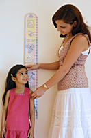 mother measuring daughter's height - Alex Mares-Manton