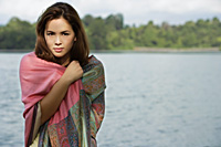Woman wrapped in shawl, standing by lake - Yukmin