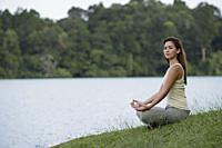 woman meditating by a lake - Yukmin
