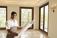 architect with blueprints - Alex Mares-Manton