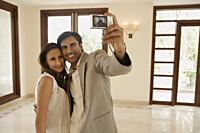 Young couple taking picture in empty home - Alex Mares-Manton