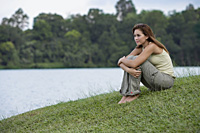 Woman hugging her knees by lake - Yukmin
