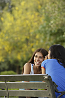 Two teen girls telling secrets in park - Alex Mares-Manton