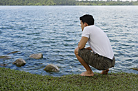 Man bending down next to lake - Yukmin