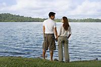 Couple standing by lake's edge - Yukmin