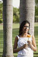 teen girl leaning against tree, with flower - Alex Mares-Manton