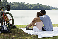 Couple sitting on blanket by a lake - Yukmin