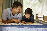 father and son reading book on bed - Alex Mares-Manton
