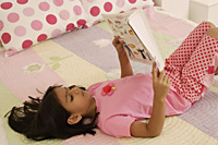 little girl reading on bed - Alex Mares-Manton