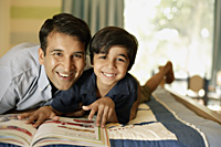 father and son reading book - Alex Mares-Manton
