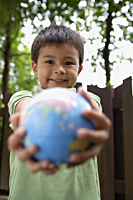 Boy holding out globe - Yukmin