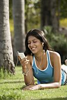 teen girl listening to music in park - Alex Mares-Manton
