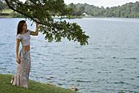 Woman standing under tree by lake - Yukmin
