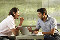 two men at laptop in cafe - Alex Mares-Manton