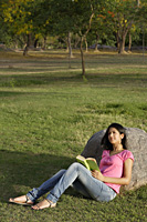 teen girl reading book in park - Alex Mares-Manton