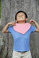 Boy standing by tree holding heart - Yukmin