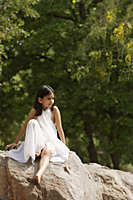 girl in white sari, sitting on rock - Alex Mares-Manton