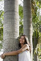 teen girl hugging tree in park - Alex Mares-Manton