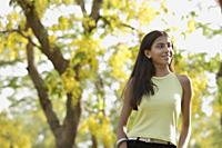 teen girl standing under blooming tree - Alex Mares-Manton