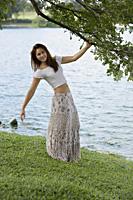 Woman standing under tree near lake - Yukmin