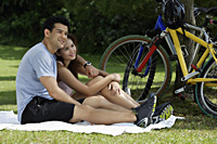 Couple resting on blanket in a park - Yukmin
