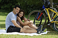 Couple sitting on blanket in a park - Yukmin