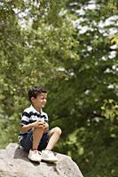 boy sitting on rocks - Alex Mares-Manton