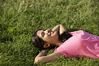 teen girl lying on back on grass - Alex Mares-Manton